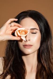 눈을 가진 검은 머리를 가진 매력적인 관능적인 여성의 초상화는 그녀의 눈 중 하나에 로즈버드를 손에 들고 닫혀 있습니다.