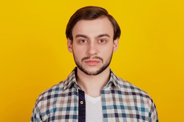 鮮やかな黄色の背景の上に分離された市松模様のシャツを着て魅力的な深刻なひげを生やした男の肖像画