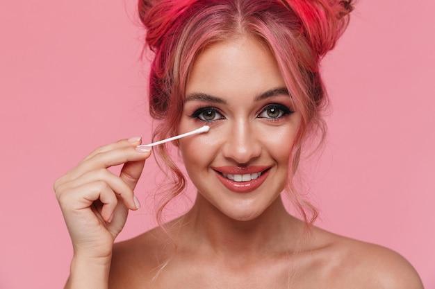 綿棒で化粧を外す魅力的な上半身裸の若い女性の肖像画