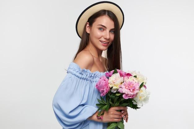長いブルネットの髪を持つ魅力的な笑顔の女の子の肖像画。帽子と青いかわいいドレスを着ています。美しい花の花束を持っています。白い壁の上に孤立して見ています