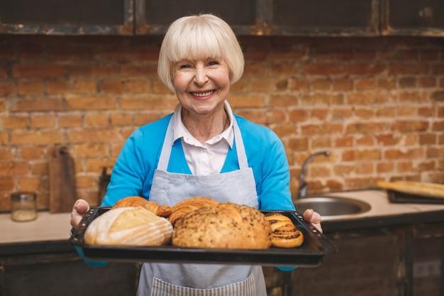 Портрет привлекательной усмехаясь счастливой старшей постаретой женщины варит на кухне. бабушка делает вкусную выпечку.