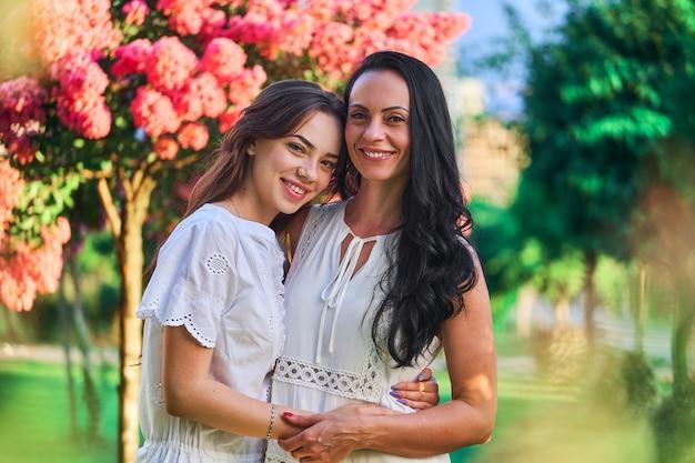 Портрет привлекательной улыбающейся радостной счастливой матери с дочерью, обнимающейся и смотрящей в камеру в парке на открытом воздухе