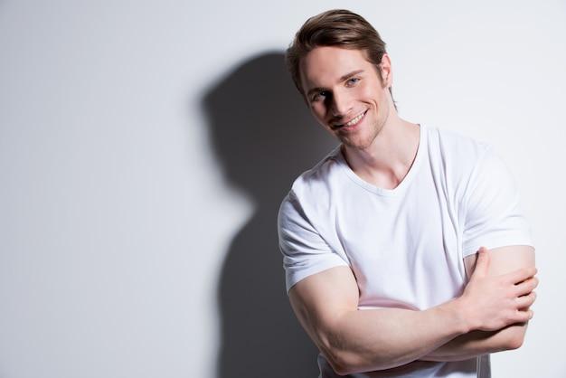 白いtシャツの魅力的な笑顔の男の肖像画は、コントラストの影で壁を越えてポーズします。