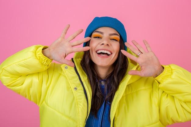 따뜻한 옷을 입고 파란색 니트 모자를 쓰고 밝은 네온 노란색 재킷에 분홍색 벽에 겨울 패션 봐 포즈 매력적인 웃는 세련된 여자의 초상화
