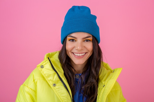 黄色のカラフルな冬のダウンジャケットでピンクの壁にポーズをとって、青いニットの帽子をかぶって、暖かい服を着て、ファッショントレンドの魅力的な笑顔のスタイリッシュな女性の肖像画