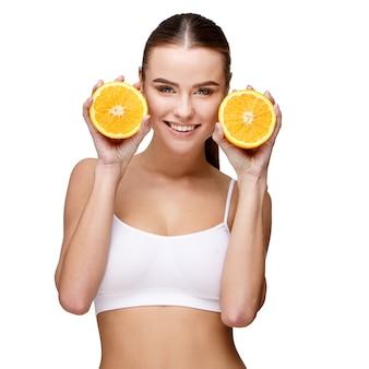 白地にオレンジを保持している魅力的な笑顔の女性の肖像画