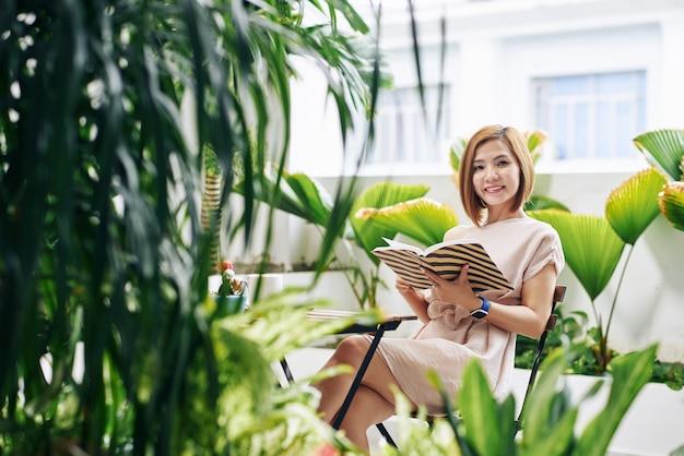 Портрет привлекательной улыбающейся молодой азиатской женщины, наслаждающейся чтением книги в кафе