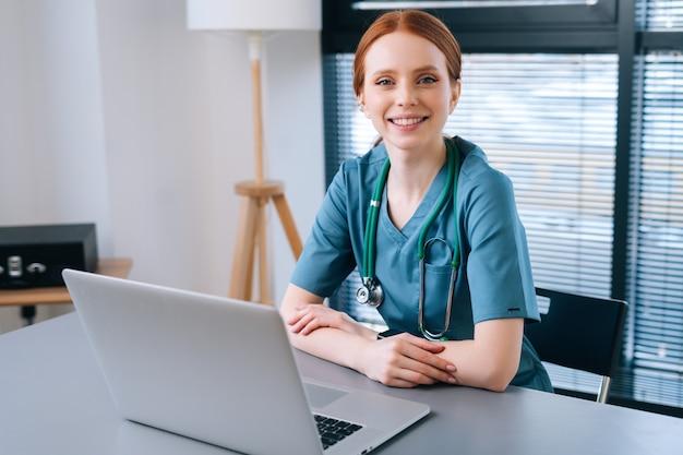 窓の背景にラップトップと机に座っている青緑色の医療制服の魅力的な笑顔の若い女性医師の肖像画