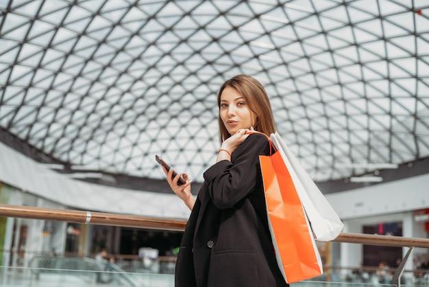 흐리게 쇼핑몰 배경으로 그녀의 손에 쇼핑백 및 모바일 매력적인 웃는 젊은 여자의 초상화