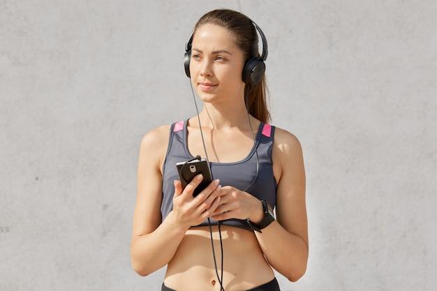 이어폰과 스마트 폰으로 음악을 듣고 낚시를 좋아하는 브래지어에 매력적인 스포티 한 여자의 초상화는 조랑말 꼬리를 가지고