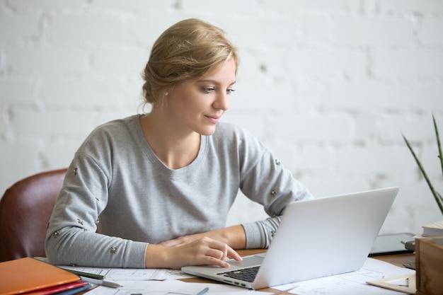 Портрет привлекательный студент девушка за столом с ноутбуком