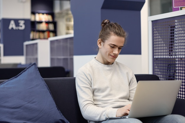 Портрет привлекательного студента с милой улыбкой, расслабляющегося дома с универсальным портативным компьютером, обмена сообщениями в интернете