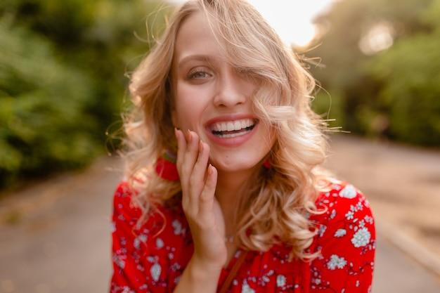 Портрет привлекательной стильной белокурой улыбающейся женщины в красной блузке, летней модной одежде в стиле бохо в парке, носить серьги, улыбаясь