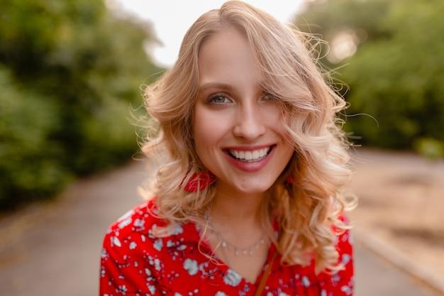 笑顔のイヤリングを身に着けている赤いブラウス夏のファッション衣装で魅力的なスタイリッシュな金髪の笑顔の女性の肖像