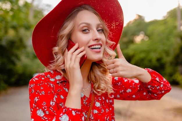 Портрет привлекательной стильной блондинки, улыбающейся женщины в соломенной красной шляпе и блузке, летней модной одежде, разговаривает по телефону с положительными эмоциями жестов
