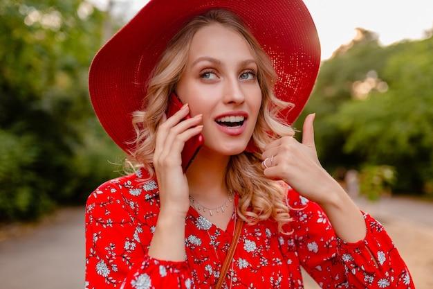 밀짚 빨간 모자와 블라우스 여름 패션 복장에 매력적인 세련된 금발 웃는 여자의 초상화 전화 긍정적 인 제스처 감정에 이야기