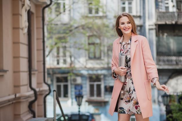 ピンクのコートと花柄のドレスで街を歩いて魅力的なスタイリッシュな笑顔の女性の肖像画