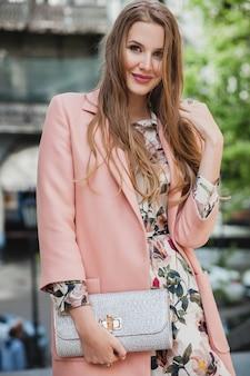 Портрет привлекательной стильной улыбающейся женщины, идущей по городской улице в розовом пальто и цветочном платье