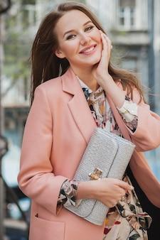 ピンクのコート春のファッショントレンドの財布を持って街を歩いて魅力的なスタイリッシュな笑顔の女性の肖像画