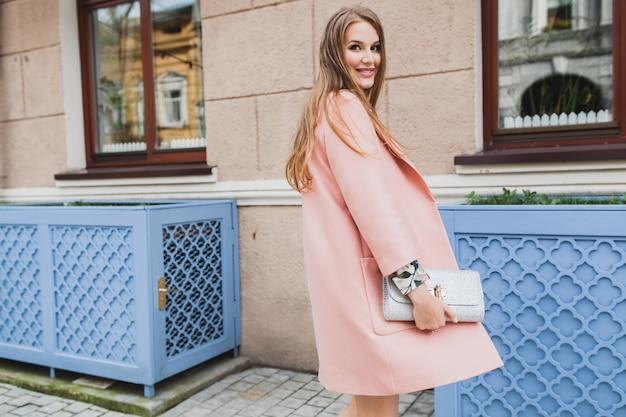 ピンクのコートで街を歩いて魅力的なスタイリッシュな笑顔の女性の肖像画