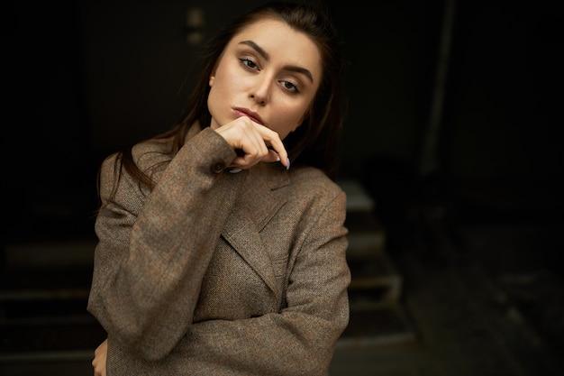 그녀의 턱에 손을 잡고 카메라를 응시하는 자신감이 심각한 모습을 가지고 매력적인 세련 된 젊은 사업가의 초상화. 따뜻한 특대 재킷에 고립 된 아름 다운 사려 깊은 여성 포즈