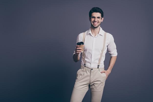 뜨거운 테이크 아웃 커피를 마시는 매력적인 성공적인 비즈니스 남자 지도자의 초상화 약간의 휴식 옷을 입고 formalwear 셔츠 베이지 색 멜빵 바지 사양.