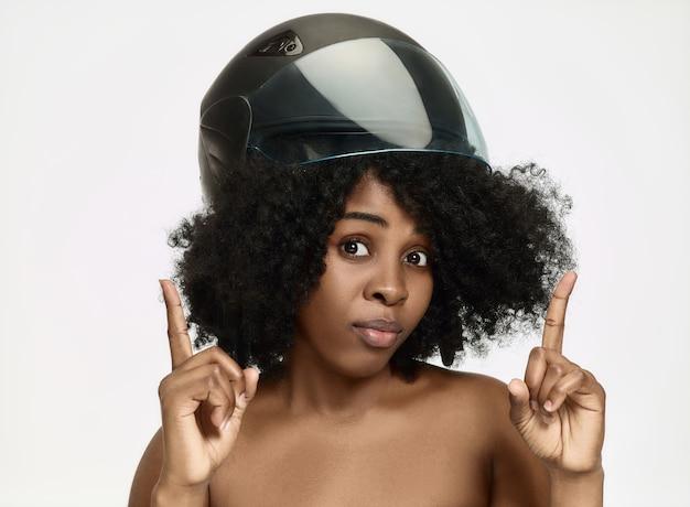 白いスタジオの背景にバイクのヘルメットをかぶった魅力的な驚いたアフリカ系アメリカ人女性のポートレート。美容と肌保護のコンセプト