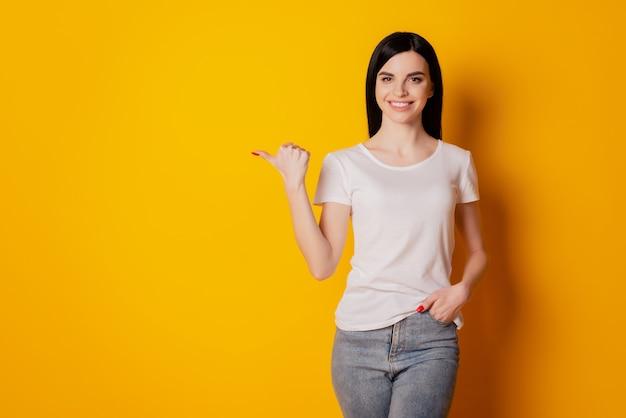 魅力的な甘い若い女の子の肖像画ポイント親指空のスペースは、孤立した黄色の背景を選択することを提案します