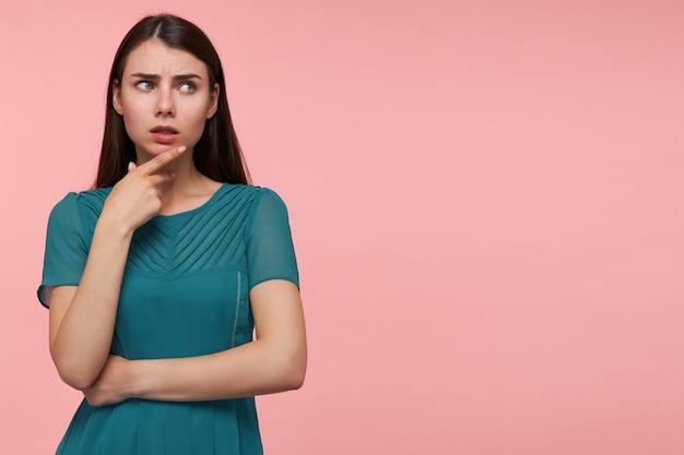 長いブルネットの髪を持つ魅力的な、思考の女の子の肖像画。手を胸に折り、あごに触れます。パステルピンクの壁の上のコピースペースで右を見てください。エメラルドドレスを着て