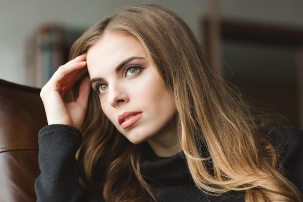 Портрет привлекательной вдумчивой молодой женщины, сидящей дома