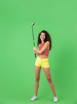 녹색 벽에 서서 클럽을 잡고 골프를 치는 여름 옷을 입은 매력적인 20대 여성의 초상화