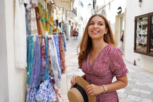 旧市街の居心地の良い通りで目をそらして帽子をかぶっている魅力的な女性の肖像画