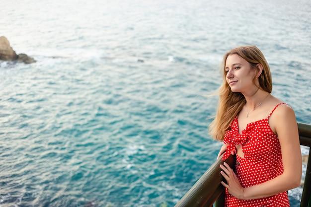 海を探している赤いドレスの魅力的な女性の肖像画。彼女は微笑んでいる。
