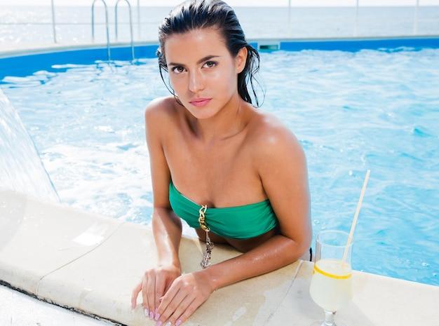 Портрет привлекательной женщины, стоящей в бассейне на открытом воздухе