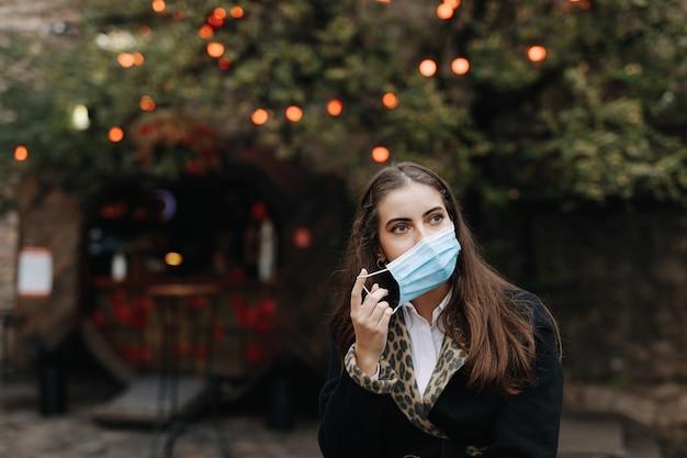 通りを歩きながら医療衛生マスクを身に着けている魅力的な女性の肖像画。コロナウイルスの間に保護措置を取っている若い女性。
