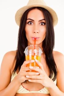 Портрет привлекательной женщины в купальнике и шляпе, пьющей сок