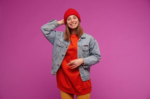 갈색 긴 머리를 가진 매력적인 여자의 초상화입니다. 청바지 재킷, 노란색 바지, 빨간 스웨터 및 모자를 착용하십시오. 그녀의 머리 뒤를 만지고 보라색 벽 위에 미소