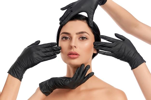 Портрет привлекательной женщины с темными волосами, получающей процедуры по уходу за кожей от двух косметологов в черных резиновых перчатках