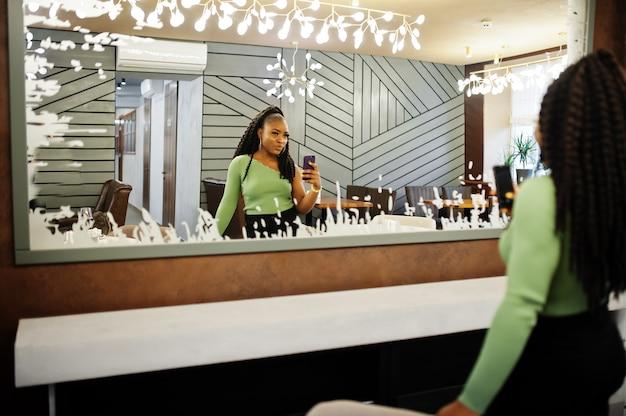 手元に携帯電話で緑のセーターと黒のジーンズを着ている魅力的な若いアフリカ系アメリカ人女性の肖像画は、鏡に立ちます。