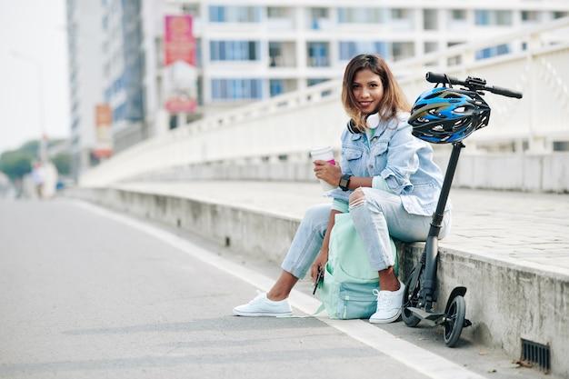 전기 스쿠터를 타고 길가에서 쉬고 있는 커피 한 잔을 들고 있는 매력적인 젊은 아시아 여성의 초상화