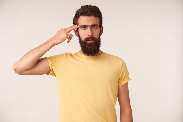 白い壁に立っている魅力的な若いひげを生やした男の肖像腕に触れる頭の感情に懐疑的な疑い深い思想家