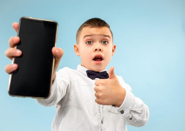 空白のスマートフォンを保持している魅力的な若い男の子の肖像画