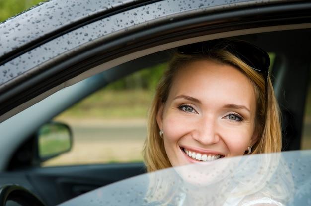 새 차에 매력적인 젊은 쾌활 한 여자의 초상화-야외