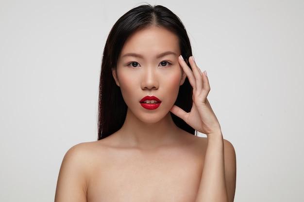 Портрет привлекательной молодой темноволосой девушки с праздничным макияжем, нежно поднимающей ее лицо, стоя у белой стены