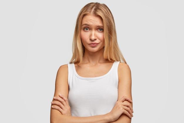 不愉快な表情で魅力的な若い女性の肖像画、腕を組んで、顔をしかめ、不思議に思って、白いベストを着て、壁に隔離された何かを聞く