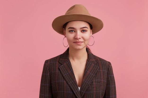 Портрет привлекательной молодой женщины с веснушками в клетчатой куртке и коричневой шляпе, улыбаясь и глядя на камеру, изолированную на розовом фоне.