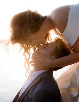 Портрет привлекательная молодая девушка целует кавказских красавец на носу в солнечных лучах
