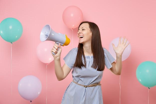 Портрет привлекательной молодой радостной женщины в голубом платье, держащего мегафон, разводящего руками на пастельно-розовом фоне с красочными воздушными шарами. праздник дня рождения, концепция искренних эмоций людей.