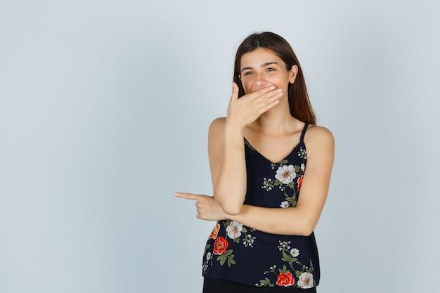 Портрет привлекательной молодой леди, держащей руку во рту, улыбаясь в блузке и глядя на нее веселый вид спереди