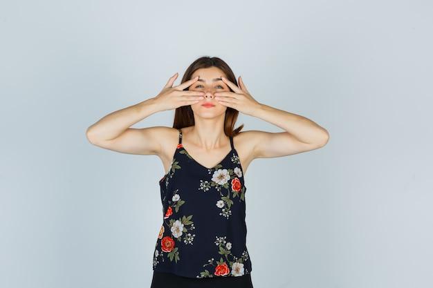 Портрет привлекательной молодой леди, смотрящей сквозь пальцы в блузке и смотрящей на разумный вид спереди